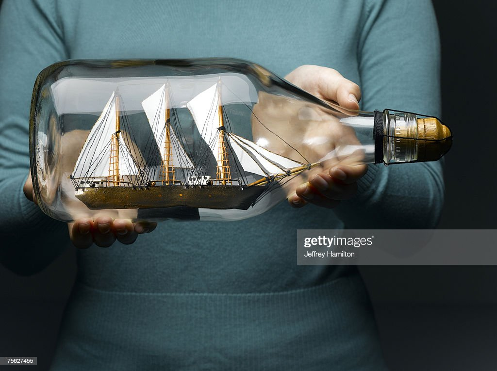 Woman holding sailing ship in bottle, mid section : Stock Photo