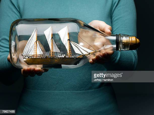 woman holding sailing ship in bottle, mid section - ship in a bottle stock pictures, royalty-free photos & images