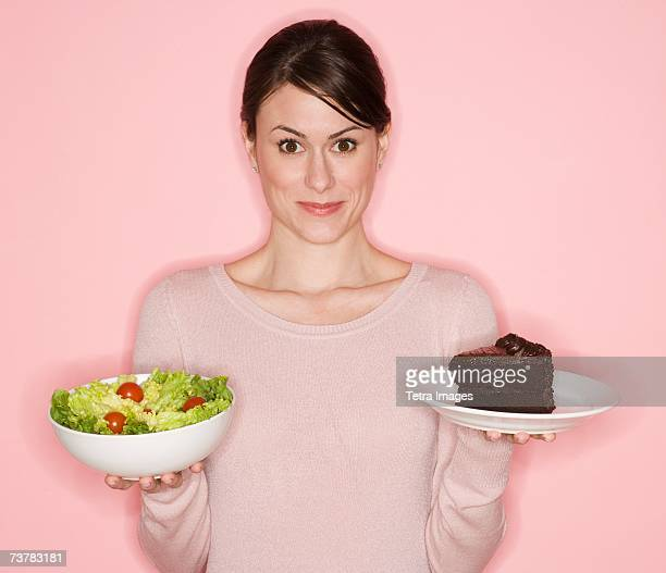 woman holding salad and cake - unhealthy living stock pictures, royalty-free photos & images