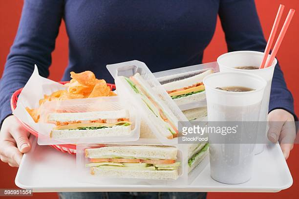 Woman holding sandwiches, cola and crisps on tray