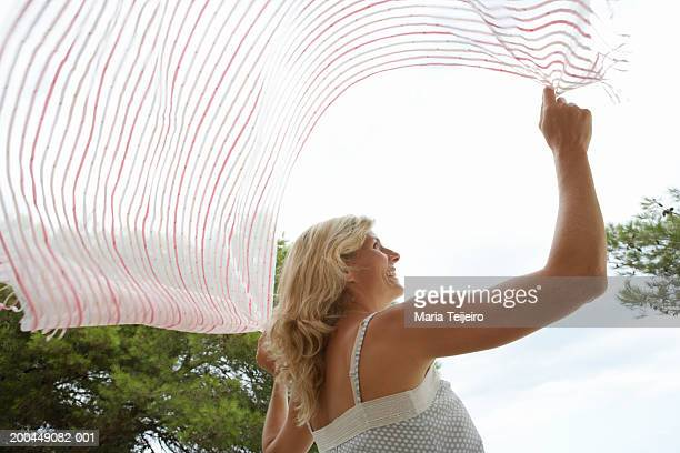 Woman holding sarong above head to catch breeze, low angle view