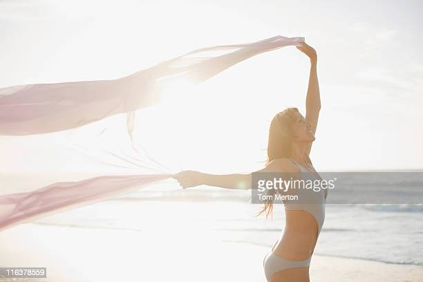 Woman holding sarong overhead on beach