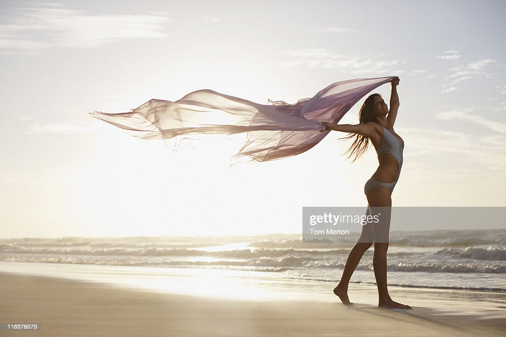 Woman holding sarong overhead on beach : Stock Photo