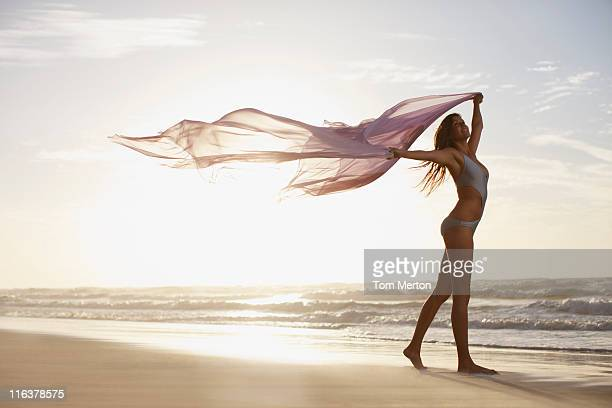 woman holding sarong overhead on beach - sarong stock photos and pictures