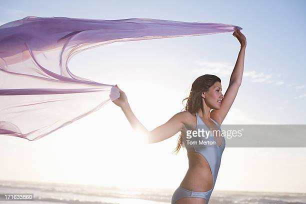 woman holding sarong overhead on beach - wind blowing up skirts stock photos and pictures