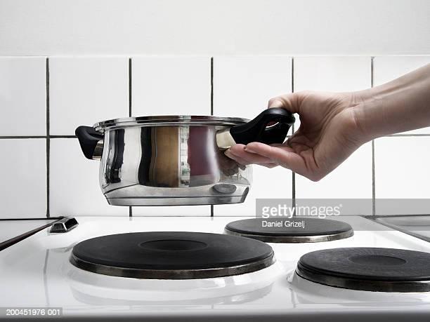 woman holding saucepan over stove, close-up - pan keukengereedschap stockfoto's en -beelden