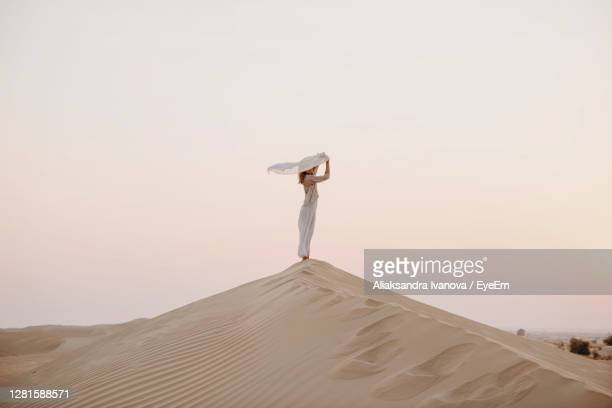 woman holding scarf in the sand dune in desert - sand stock pictures, royalty-free photos & images