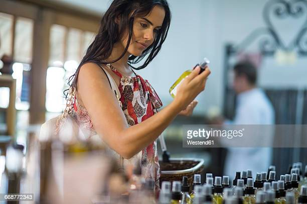 Woman holding scent bottle in shop