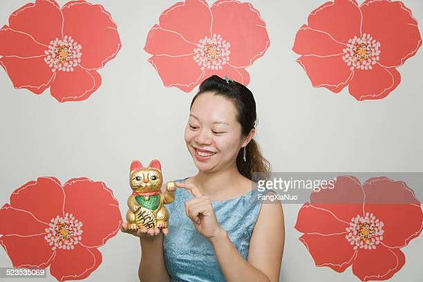 woman holding sculpture of traditional fortune cat maneki neko - maneki neko stock photos and pictures