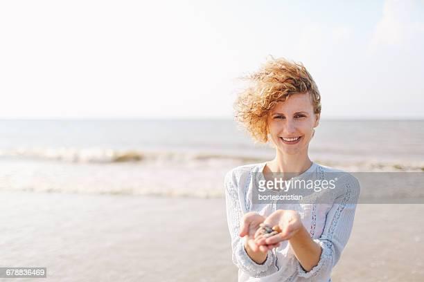 Woman Holding Seashells On Sunny Beach