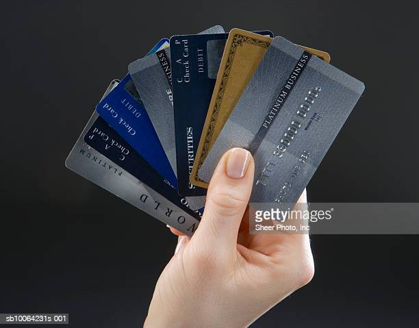 woman holding set of fanned-out credit cards, close-up of hand - petit groupe d'objets photos et images de collection