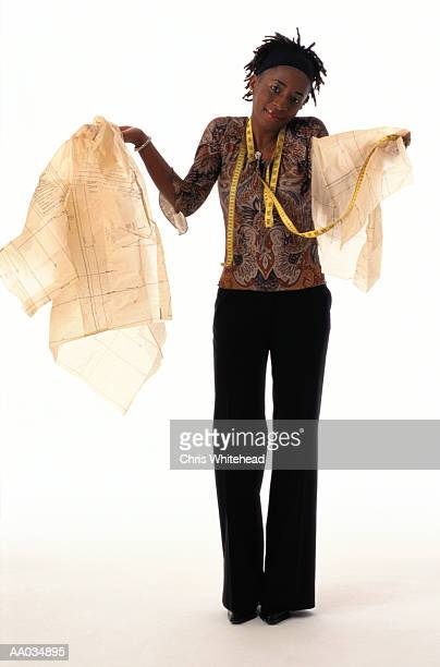 Woman Holding Sewing Patterns & a Measuring Tape