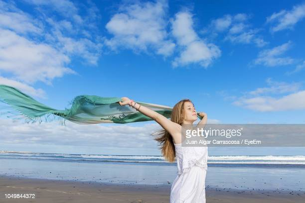 woman holding shawl while standing at beach against sky - ストール ストックフォトと画像