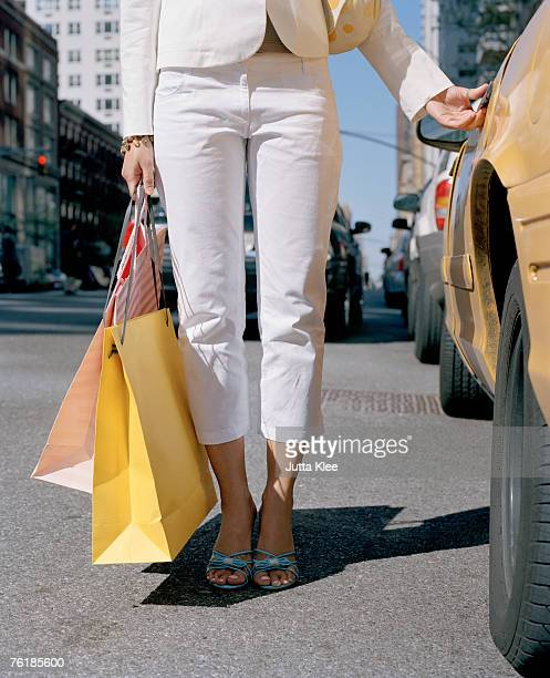 Woman holding shopping bags by a taxi