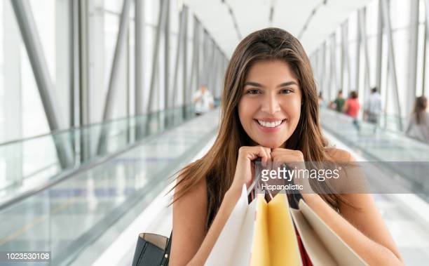 Woman holding shopping bags close to her face from duty free shopping at the airport looking at camera smiling