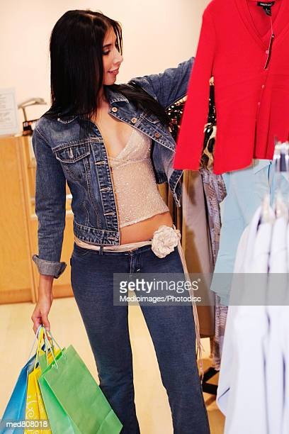 Woman holding shopping bags looking at clothes in a store