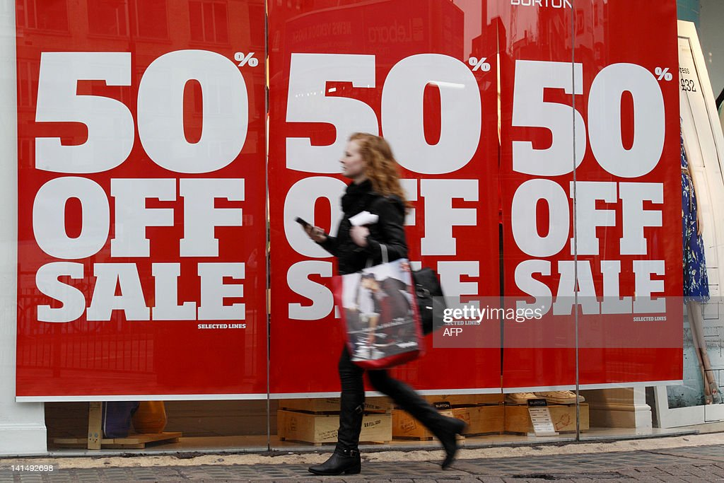 A woman holding shopping bags walks past : News Photo