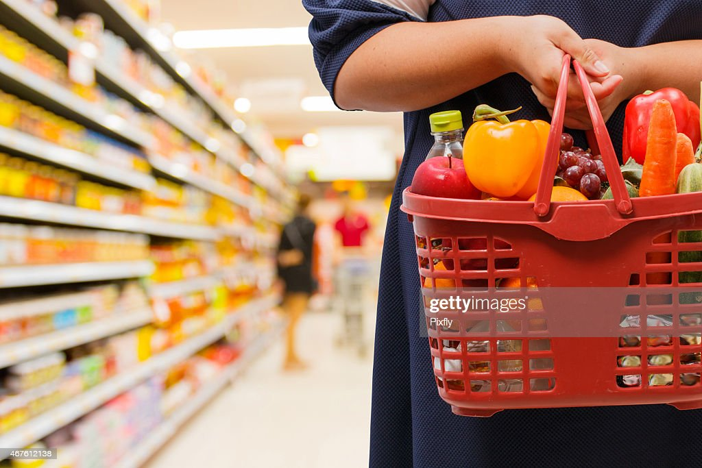 woman holding shopping basket in supermarket : Stock Photo