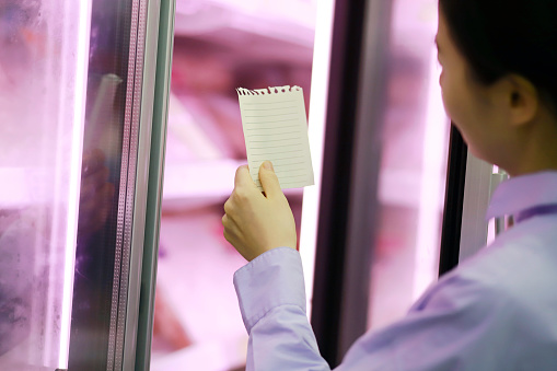 Woman  holding shopping list at refrigerated section in supermarket - gettyimageskorea