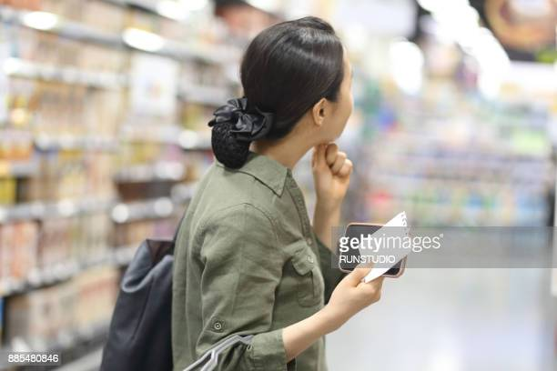 woman  holding shopping list in grocery store - contact list stock photos and pictures