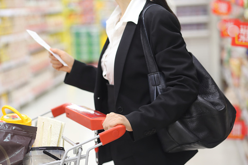 Woman holding shopping list while going through aisles in mart - gettyimageskorea