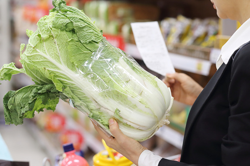 Woman holding shopping list with cabbage in supermarket - gettyimageskorea