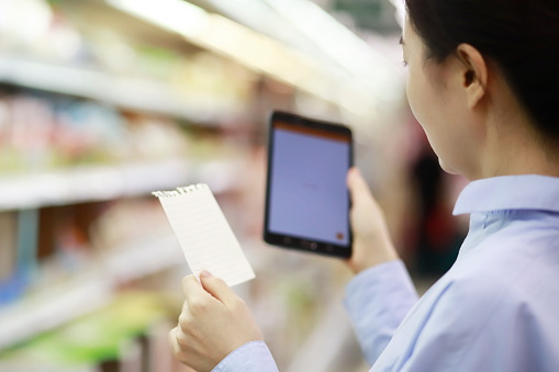 Woman holding shopping list with digital tablet in supermarket - gettyimageskorea
