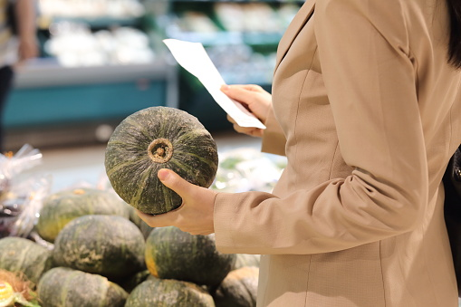 Woman holding shopping list with pumpkin in supermarket - gettyimageskorea