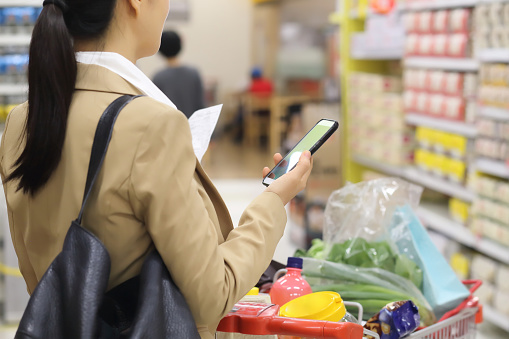 Woman holding shopping list with smartphone in supermarket - gettyimageskorea