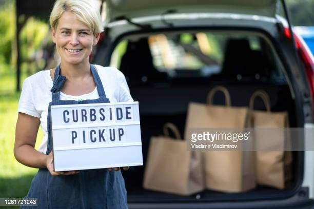 woman holding sign curbside pick up - curbside pickup stock pictures, royalty-free photos & images