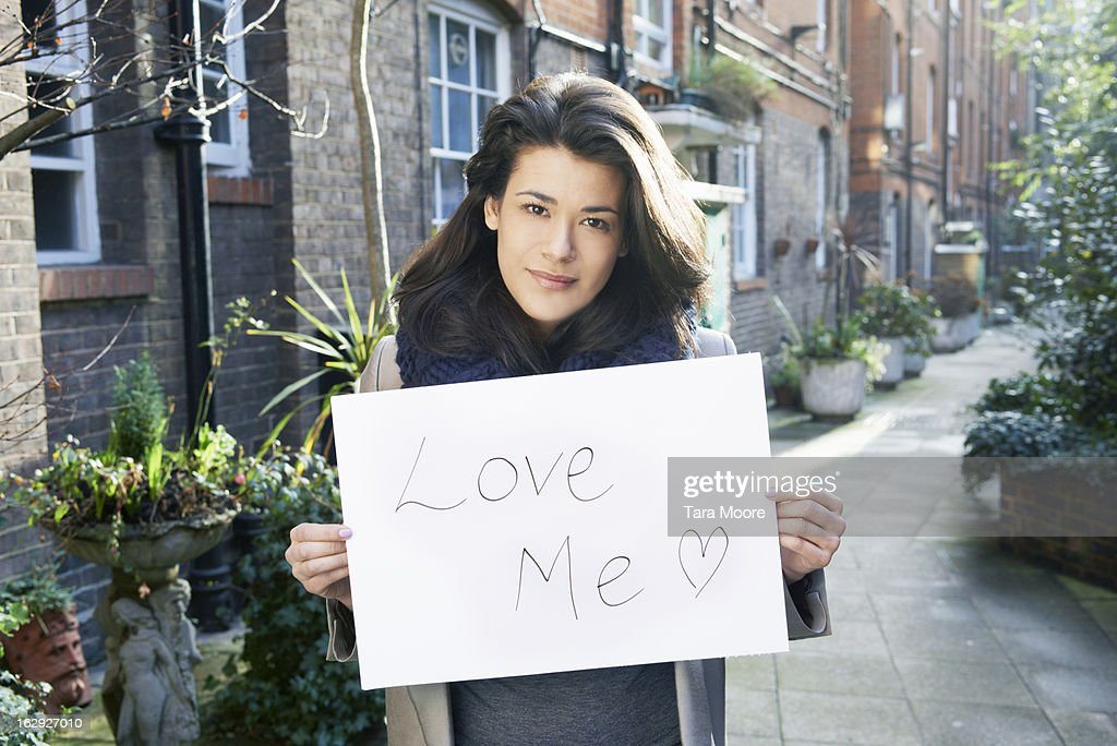woman holding sign saying 'Love me' : Stock-Foto