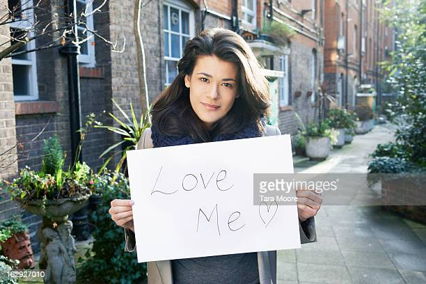"woman holding sign saying ""love me"" - placard stock pictures, royalty-free photos & images"