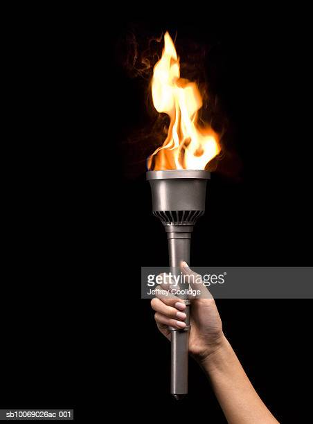 woman holding silver torch, on black background - flame stock pictures, royalty-free photos & images