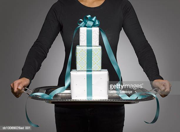 Woman holding silver tray with tree wrapped presents, mid section, studio shot