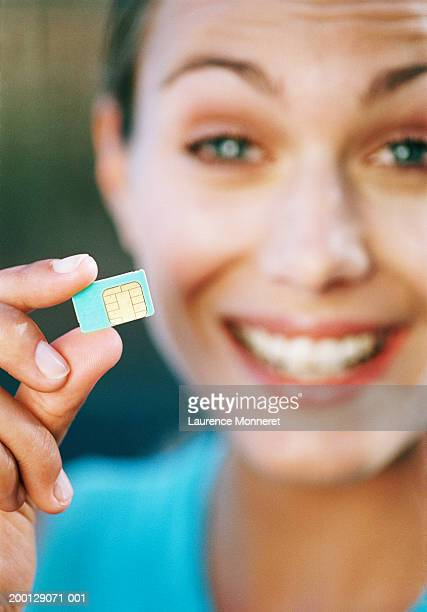 Woman holding SIM card, portrait (focus on hand holding SIM card)