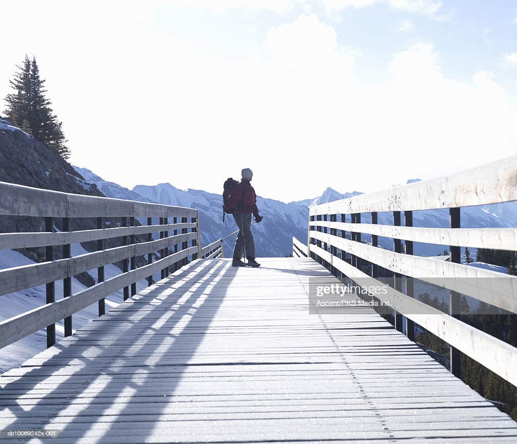 Woman holding ski pole standing on boardwalk, snow capped mountain in background : Stockfoto