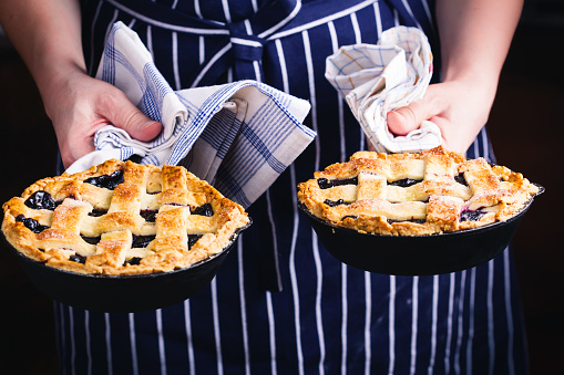 Woman holding skillet with blueberry lattice top pie - gettyimageskorea