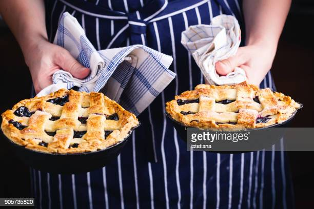 Woman holding skillet with blueberry lattice top pie