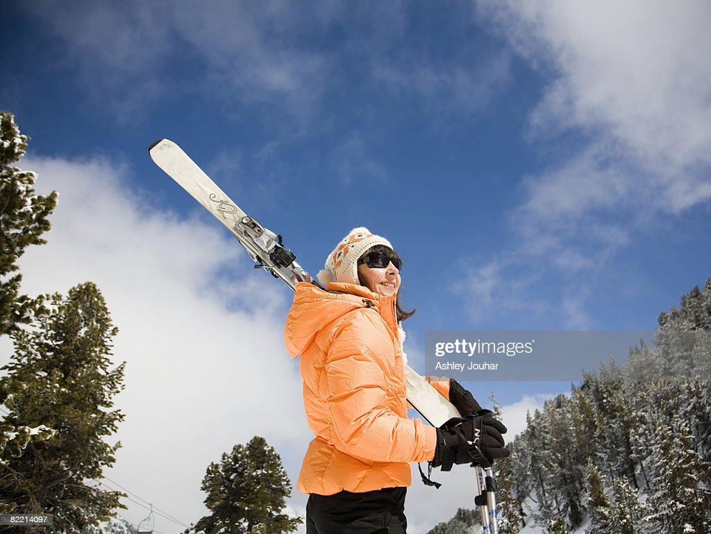 Woman holding skis in snowy landscape : Stock Photo