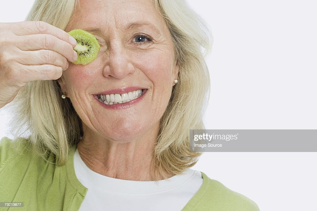 Woman holding slice of kiwi : Stock Photo
