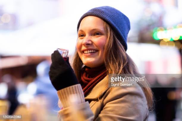 woman holding small glass of beverage, christmas market, freiburg, deutschland - sigrid gombert stock-fotos und bilder