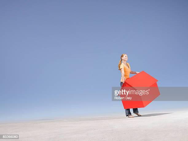 Femme tenant une petite maison témoin dans le désert
