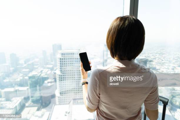 woman holding smart phone and standing in front of window - front view ストックフォトと画像