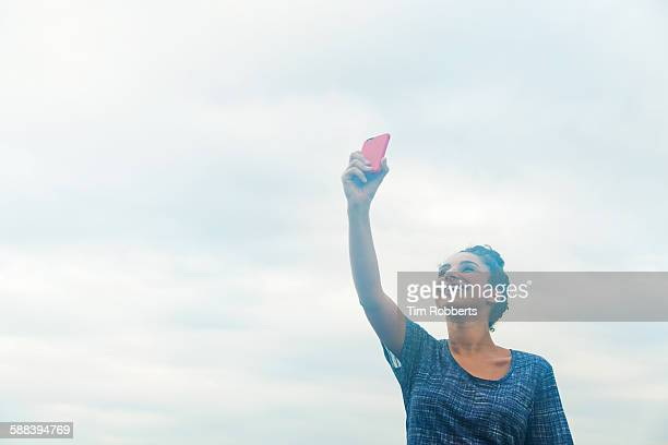 Woman holding smart phone in the air.
