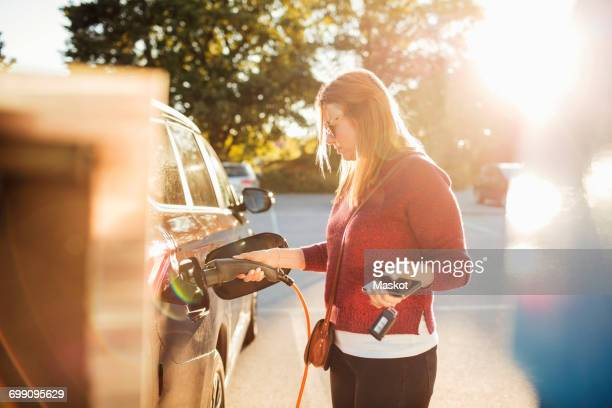 woman holding smart phone while charging electric car at station on sunny day - electric car fotografías e imágenes de stock