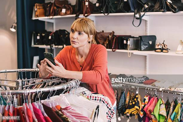 Woman holding smart phone while leaning on clothes rack at thrift store