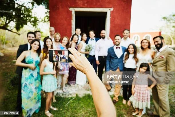 woman holding smartphone and taking picture of wedding party standing in front of chapel after wedding ceremony - wedding after party stock pictures, royalty-free photos & images