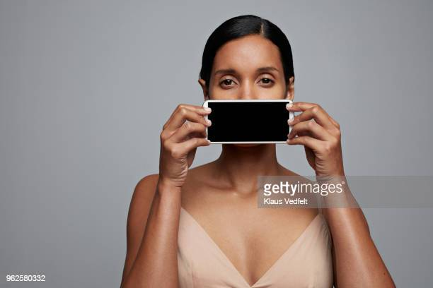 Woman holding smartphone in front of her mouth