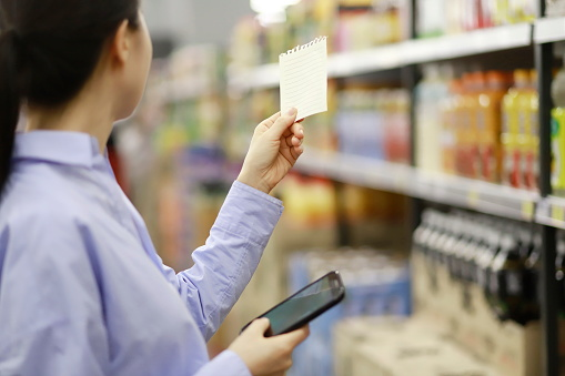 Woman holding smartphone with shopping list in supermarket - gettyimageskorea