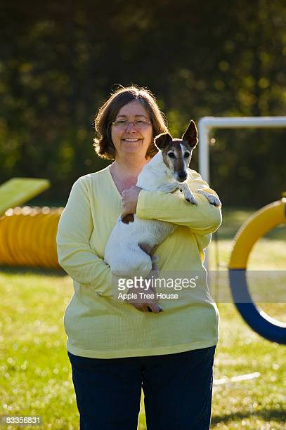 Woman holding Smooth Fox Terrier outdoors